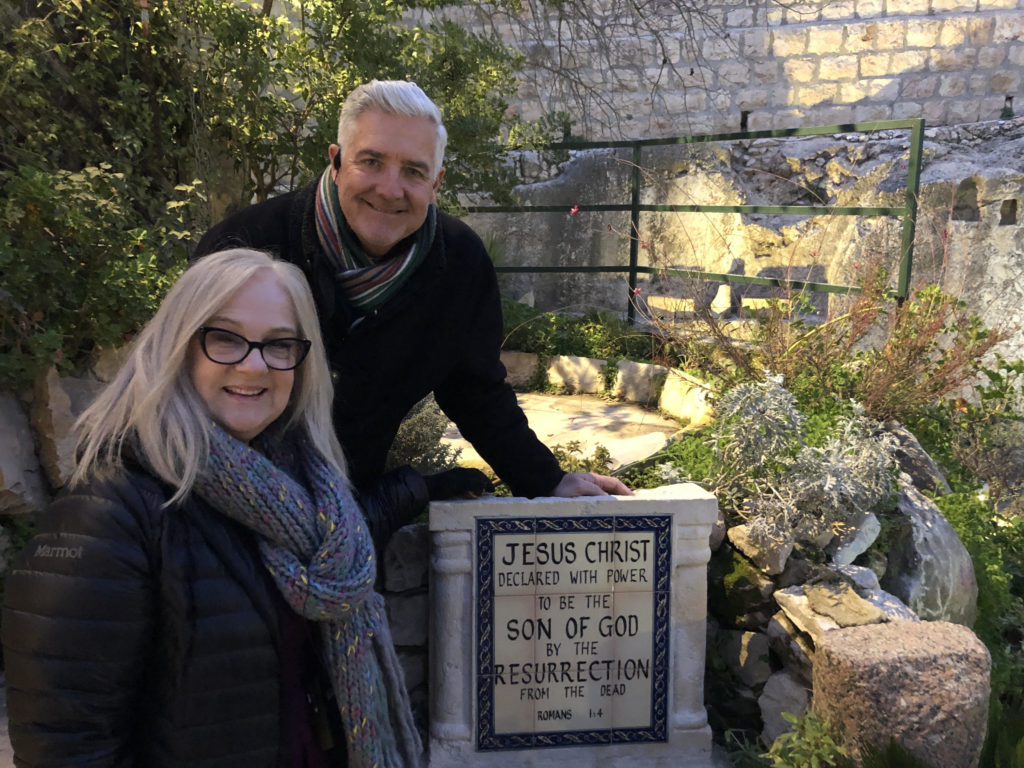 "Image of Joe and Becky Cruse in Israel standing next to a sign which reads, ""Jesus Christ declared with power to be the son of God by the resurrection from the dead."" Romans 1:4"